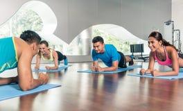 大角度观点的在小组女子柔软体操期间的健身辅导员分类 免版税库存图片