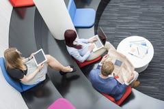 大角度观点的坐在办公室的商人游说 免版税库存图片