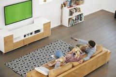 大角度观点的家庭坐沙发在看电视的休息室 免版税库存图片