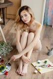 大角度观点的有油漆的美丽的肉欲的赤裸艺术家在面孔和身体坐地板和看 免版税库存图片