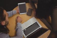 大角度观点的有膝上型计算机和片剂的朋友在咖啡馆 库存图片