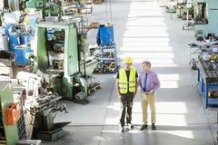 大角度观点的男性监督员和体力工人有讨论在金属工业 库存图片