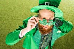 大角度观点的绿色服装佩带的三叶草的有胡子的人塑造了镜片和看照相机 图库摄影