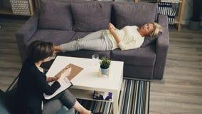 大角度观点的被注重的妇女谈话与说谎在沙发的治疗师在办公室 影视素材