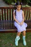 大角度观点的翻倒女孩坐长木凳 库存照片