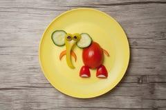 大象由未加工的食物制成在板材和木书桌 免版税库存图片