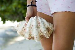 大贝壳在海的一只女孩手上 免版税库存图片