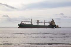 大货轮和沿海巡逻艇在海洋 免版税库存照片