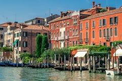 大运河的美丽如画的堤防在一个晴朗的夏日 水的明亮的威尼斯式房子,长满与明亮的greene 免版税库存照片