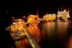 大近海抽油装置在晚上 免版税库存照片