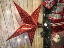 大逗人喜爱的红色假日星,圣诞节,以发光的gerlyand木垂直的板为背景的新年的装饰 免版税库存图片