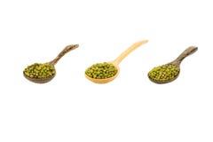 大量在木匙子的绿豆在白色 免版税库存图片