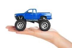大金属红色玩具汽车越野与在白色背景在手中隔绝的妖怪轮子 免版税库存照片