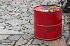 大铁老红色桶可能倾吐汽油柴油,在一条灰色街道石头瓦片路的工业对象 库存照片