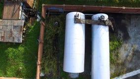大银色储水池顶视图,在储油集中处的石油水库绿草背景的 股票 空中上面 免版税库存图片