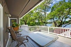 大长的阳台家外部与浴盆和椅子,湖视图。 免版税库存照片