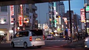 大阪,日本- 2015年3月:移动通过城市拥挤的街的交通看法有看法,如果商店 股票录像