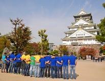 大阪,日本- 2016年11月17日:五颜六色的T恤杉的游人在大阪城堡前面 库存图片