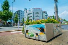 大阪,日本- 2017年7月18日:关闭与一些黄色花的一张扔石头的花盆在它和海的美好的凹道 免版税库存照片