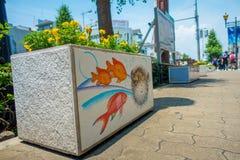 大阪,日本- 2017年7月18日:关闭与一些黄色花的一张扔石头的花盆在它和海的美好的凹道 免版税库存图片
