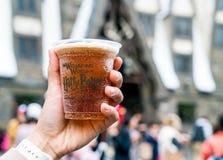 大阪,日本- 2016年11月21日:拿着塑料杯小山的手 免版税库存照片