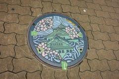 大阪,日本- 2017年7月18日:日语绘了代表在大阪街道的艺术性的人孔盖大阪城堡  免版税库存图片