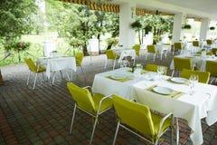 大阳台与桌和椅子人的,休闲的一个空的机关,没人的夏天咖啡馆 免版税库存照片