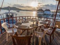 大阳台咖啡馆木桌在Coron镇的日落视图的 免版税图库摄影