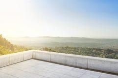 大阳台瓦片有绿色全景视图和一点村庄 库存图片