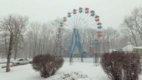 大雪在城市,在公园 观点的积雪的弗累斯大转轮阴沉的一空的游乐场 影视素材