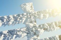 大雪盖的篱芭在飞雪以后的一个晴朗的冬日 被过滤的图象:十字架被处理的葡萄酒作用 免版税库存照片