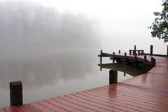 大雾在冬日盖木船坞和湖 免版税库存照片