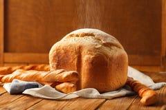 大面包和法国长方形宝石在土气木桌上 库存图片