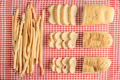 大面包和breatsticks的构成在红色和白色验查员桌布用面包从上面切看法 图库摄影