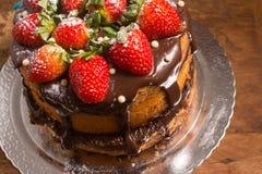大面包蛋糕用巧克力糖浆用草莓 免版税库存照片