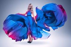 大飞行蓝色礼服的微笑的妇女 免版税库存照片