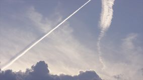 大飞行高在清楚的蓝天的乘客喷气机,离开长的白色足迹 离开对角线的飞机 免版税库存照片