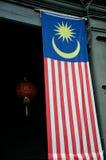 大马来西亚旗子在与红色中国灯笼后面的门道入口垂悬 库存图片