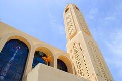 大高塔、一个尖顶在有十字架的埃及正统白色教会里,曲拱、圆顶和祷告窗口反对蓝色sk 免版税图库摄影