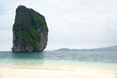 大高岩石峭壁充满土耳其玉色围拢的绿色植被在一个热带白色海滩旁边上色了海洋水 库存照片