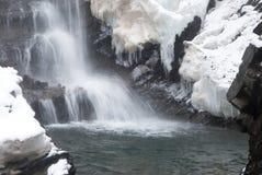 大高瀑布在有积雪的树和降雪的山冬天森林里 免版税库存照片