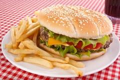 大鲜美乳酪汉堡、炸薯条和可乐 免版税库存照片