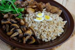 大麦粥、油煎的蘑菇和鸭子肝脏,煮沸的鹌鹑蛋,蕃茄,芝麻菜-健康食物 免版税库存照片