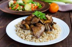 大麦粥、油煎的蘑菇和鸭子肝脏,煮沸的鹌鹑蛋,蕃茄,芝麻菜-健康食物 免版税图库摄影