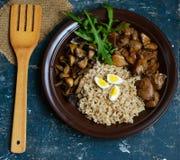 大麦粥、油煎的蘑菇和鸭子肝脏,煮沸的鹌鹑蛋,蕃茄,芝麻菜 免版税库存图片