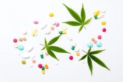 大麻叶子和医疗药片在白色 库存照片