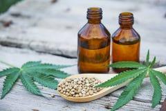大麻在木背景,种子,大麻在瓶子的油萃取物离开 库存照片