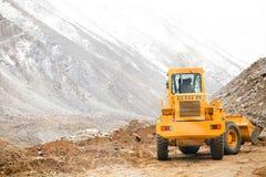 大移动在雪山的道路的大量手段车耕的沙子和石头 免版税库存照片