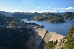 大水坝和水库与积雪的山 免版税库存照片