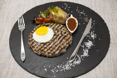 大水多的烤牛排使有大理石花纹的牛肉用鸡蛋烘烤了土豆用烤肉汁 服务在有叉子和匙子的一块石板材  免版税库存照片